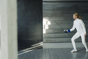 Young concentrated fencer woman practice fencing exercises and training for Olympic games competition in studio indoors