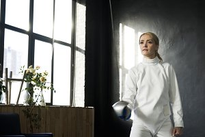 Young concentrated fencer woman training fencing exercise in studio indoors