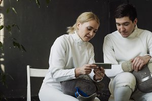 Two young fencers man and woman watching fencing tutorial on smartphone and sharing experience after training indoors