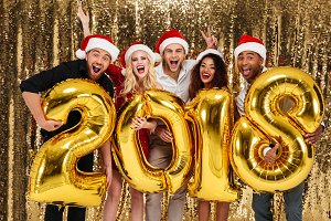 Group of smiling friends celebrating New Year while standing