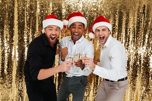 Group of excited handsome multiracial friends in christmas hats