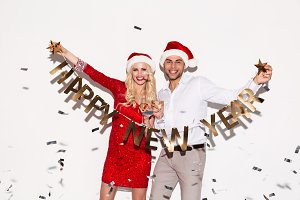 Excited happy young loving couple holding happy new year garland.
