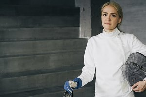 Portrait of young fencer woman concentrated and looking into camera indoors