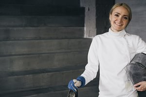 Portrait of young fencer woman smiling and looking into camera indoors