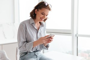Portrait of a smiling pretty woman texting on mobile phone