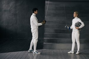 Two fencers man and woman have greeting each other and start fencing match indoors