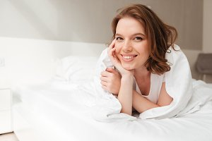 Cheerful lady lies on bed indoors home