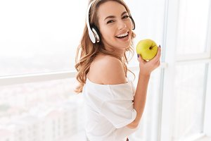 Beautiful laughing young lady with headphones eating apple.