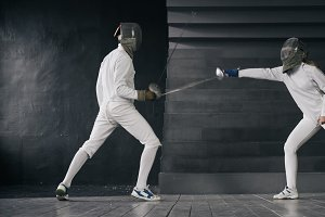 Two fencers man and woman have fencing match indoors
