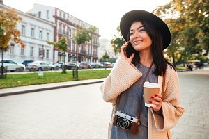 Portrait of a cheerful stylish woman holding coffee cup