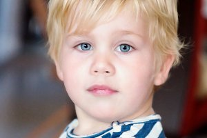 Two year blond old boy with blue eyes in a striped T-shirt on an abstract background