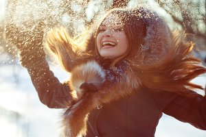 Cheerful woman playing with snow