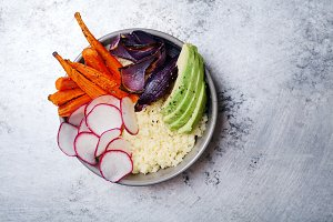 Vegetarian bowl for lunch with baked carrots, coucous and red onion