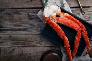 Fresh crab claws on black wooden tray