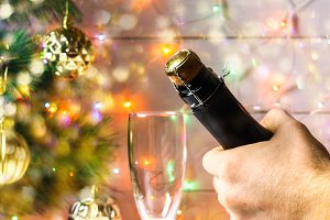 Men's hands open a bottle of champagne on the background of a New Year tree and garlands and glasses.