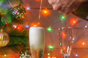 Men's hands pour champagne from a bottle in glasses against the background of a New Year tree and garlands.