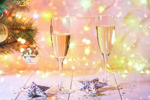Two glasses of champagne stand on a white wooden table on the background of a New Year tree and garlands. Christmas bokeh.