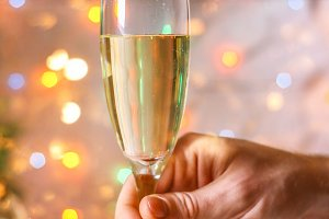 Male and female hands hold a glass of champagne against the backdrop of the New Year tree and garlands.