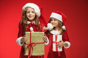 Two happy girls in santa claus hats with gift boxes at studio