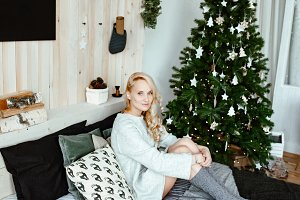Christmas.Blonde sits on bed