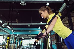 Young woman athlete trains using TRX