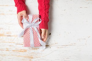 Christmas concept - hands in steater holding present