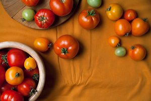 Fresh tomatoes on mustard yellow textile background