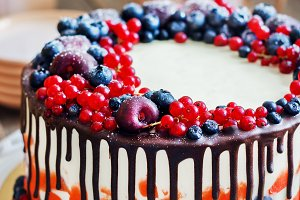 Bright festive cake with berries and chocolate on a dark wood background, rustic style