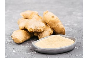 ginger poder and ginger root on gray concrete background