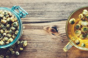 chamomile tea cup and jar of daisies
