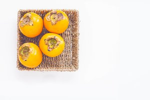 Kaki fruits in the basket on white background.