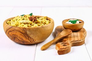 Indian biryani with chicken, yogurt and spices in a plate on a wooden table. New Year's, Christmas dish.