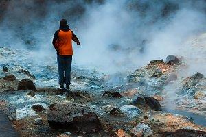 Tourist watching hot stream in Iceland