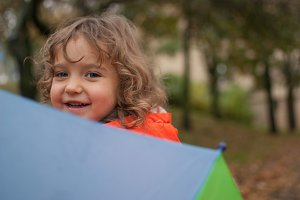 Little girl hiding behind umbrella