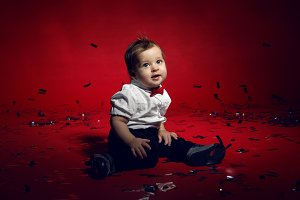 baby boy crawling on the floor with confetti in Studio