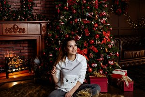 girl in pajamas opens Christmas gift
