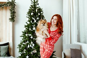 girl in a red pajamas and spitz-dog