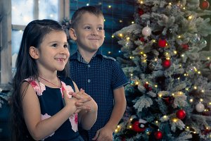 Happy kids beside the Christmas tree
