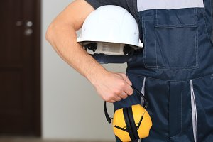 Worker holding white hard hat