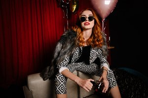 Bossy redhead woman drinking whiskey and owning the party