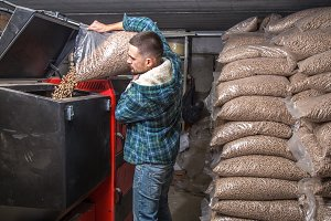 the man loads the pellets in the solid fuel boiler, economical heating