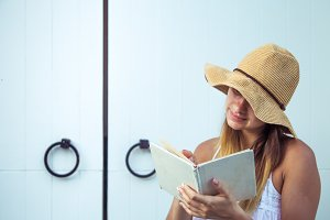 girl reading a book at the door