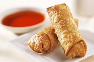 egg rolls with sauce on light wood