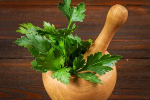 A bunch of green parsley on a wooden table in a mortar.