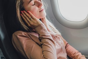Girl near the window in airrplane listening music