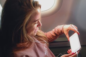 Girl is reading from smartphone in airplane