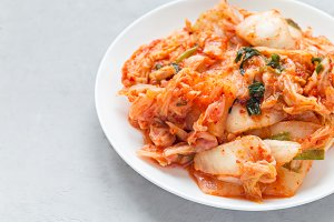 Kimchi cabbage. Korean appetizer on white plate, horizontal, copy space