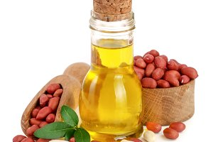 peanut oil in a glass bottle with peanuts in bowl