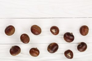 chestnut on white wooden background with copy space for your text. Top view. Flat lay.