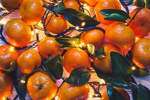 Christmas New Year background of tangerines and burning garlands